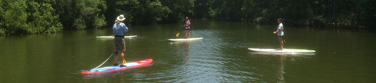 Image of three women learning to SUP at James Island County Park