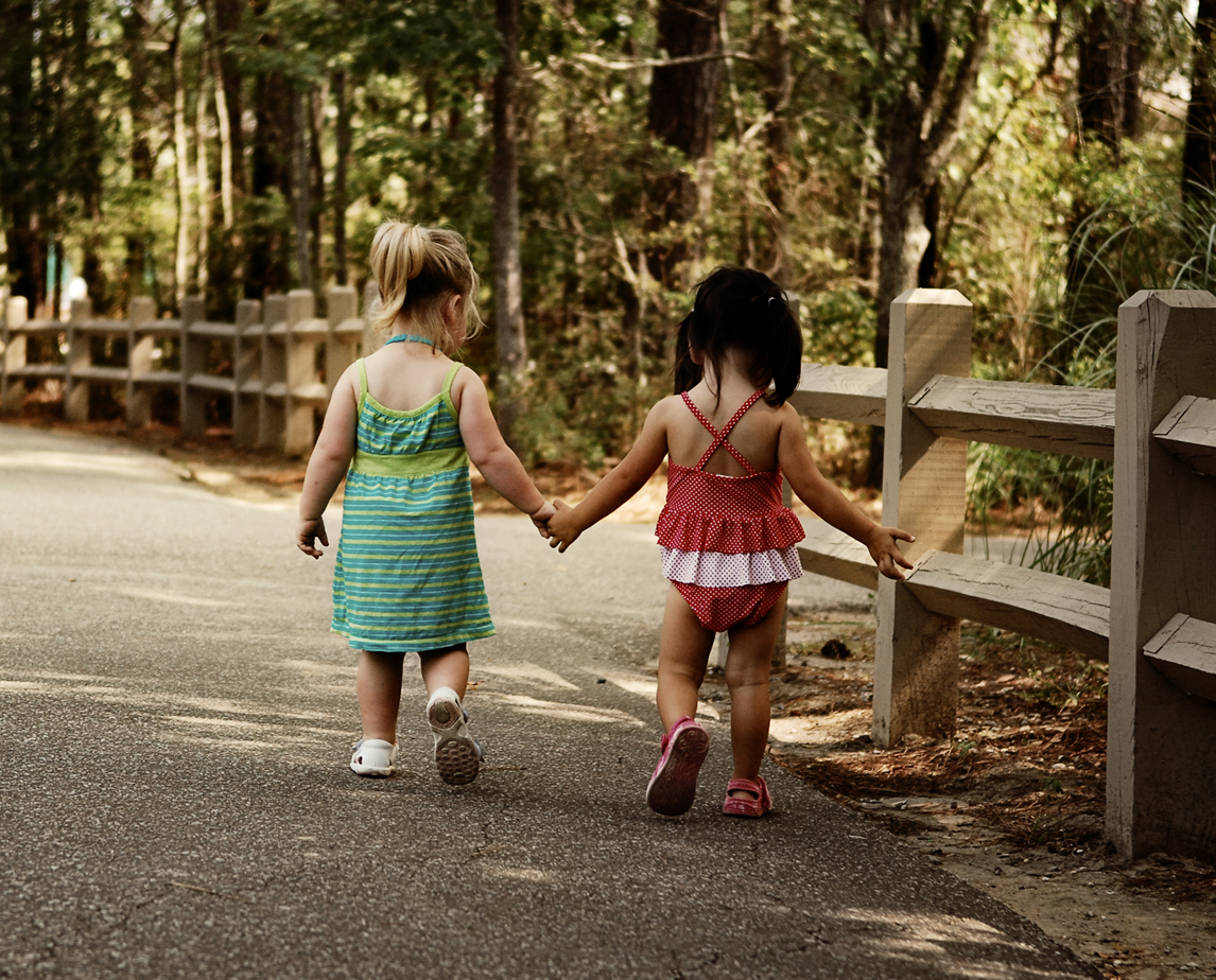 Little girls walking hand-in-hand on a park trail