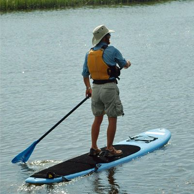 A man stand up padleboarding on the calm waters of the lake at James Island County Park