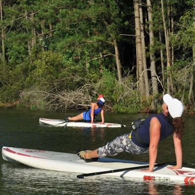 Two women on stand up paddleboards practicing yoga on the lake at James Island County Park