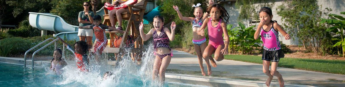A group of children jumping into the water at a waterpark party