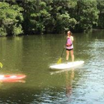 Image of two women learning to SUP from an instructor on the lake at James Island County Park