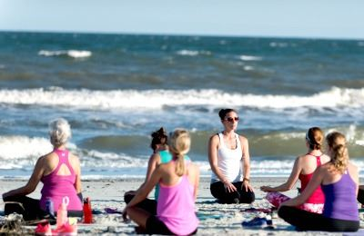 Image of women practicing yoga on the beach