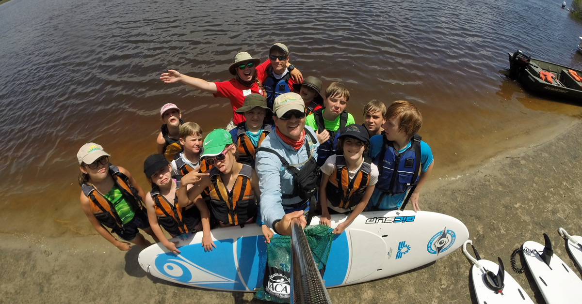 Adventure campers take a selfie on the water during a stand up paddleboard trip