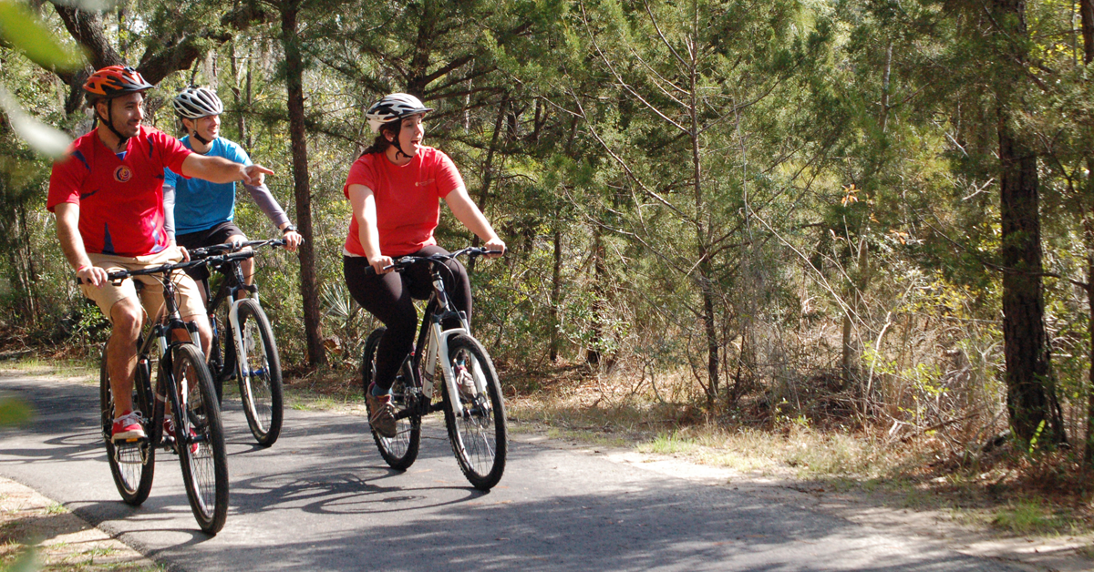 Three people riding bicycles on a trail at James Island County Park