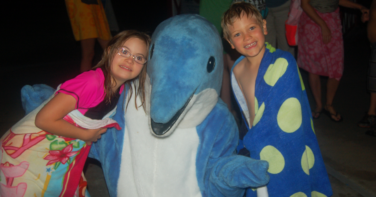 Two children with a blue dolphin mascot at the waterpark