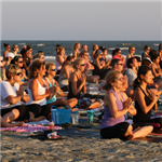 People practicing yoga on the beach