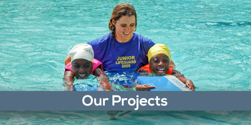 Foundation projects with a swim instructor helping two young girls learn to swim