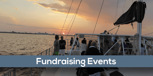 Fundraiser Events with a group of people on board a sailboat in the harbor at sunset