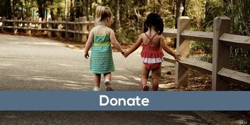 Donate button with two young girls walking hand in hand along a park path