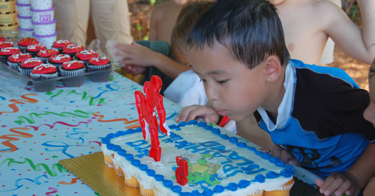 Young boy blowing out candles on his birthday cake during a party at Splash Island Waterpark