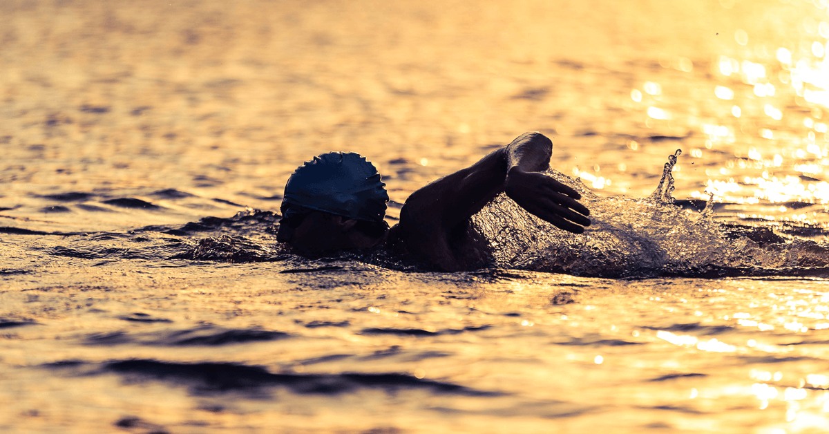 A triathlete swimmer silhouetted against the sun