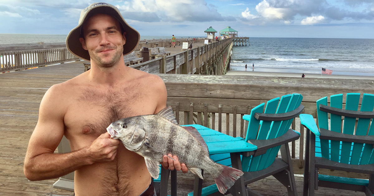 Man in a hat on the Folly Beach Pier holding a 4 pound 15 ounce Black Drum
