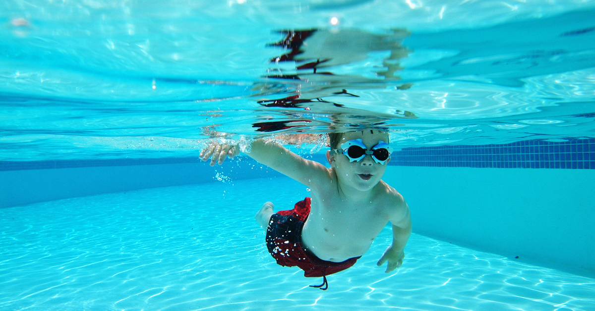Child in swim goggles swimming underwater in a pool