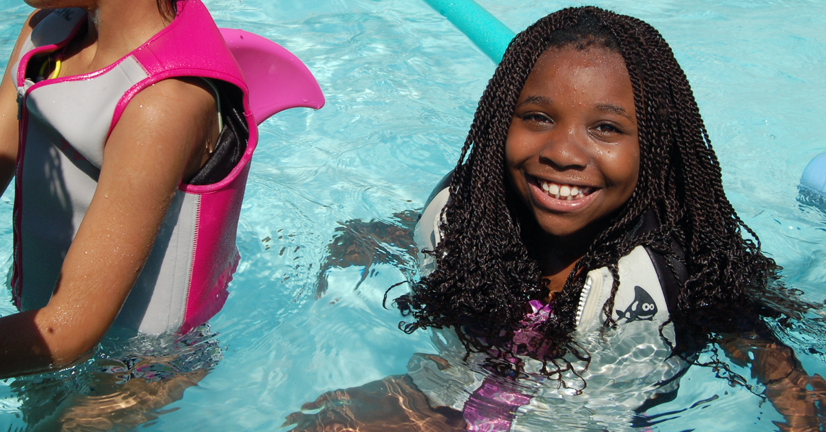 Young girl smiling in a swimming pool