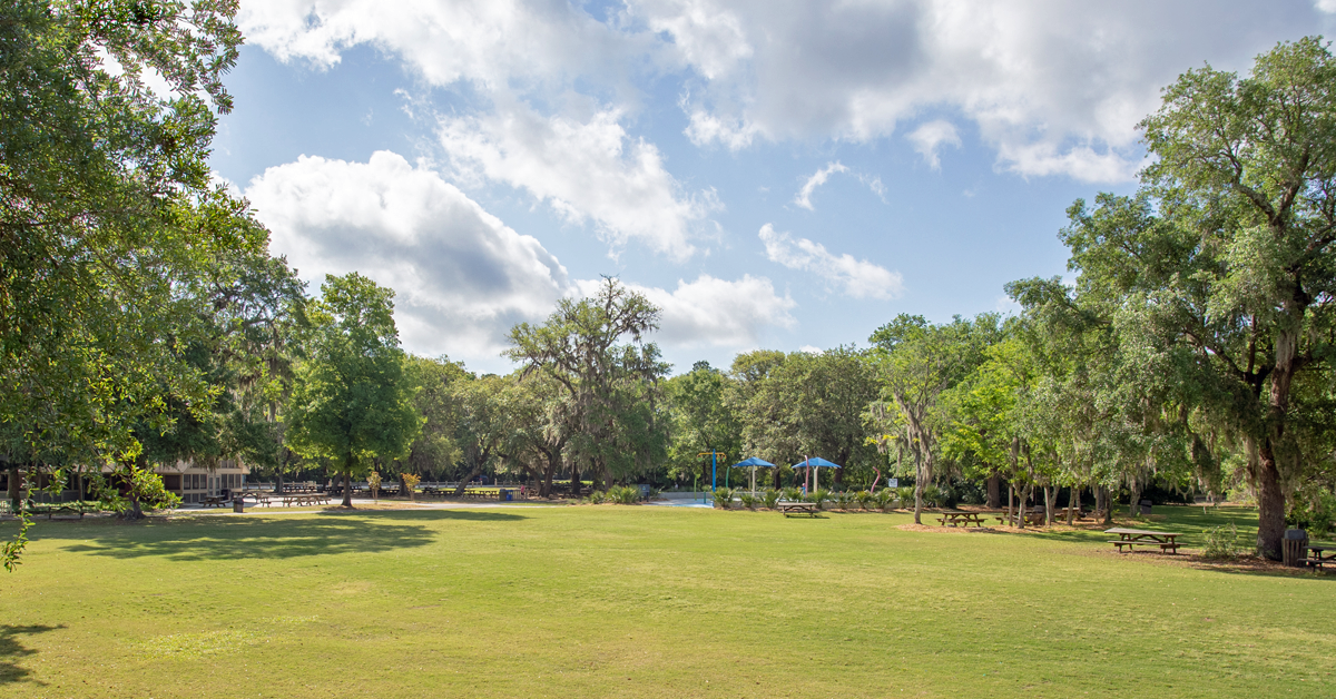 Panoramic image of a grassy meadow surrounded by oak trees, trails, and a playground