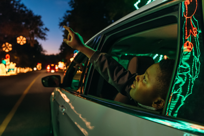 Young boy pointing out car window at light displays