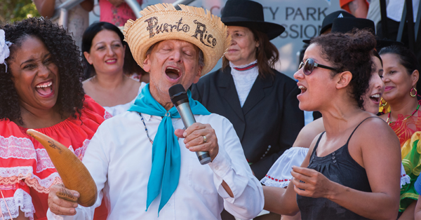 Man in a straw hat singing while people around him cheer
