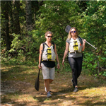 Two women walking with paddles