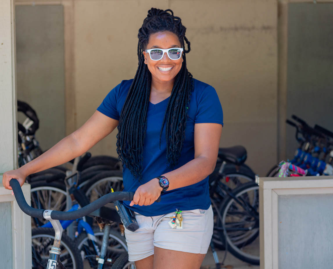Staff member smiling with bicycle