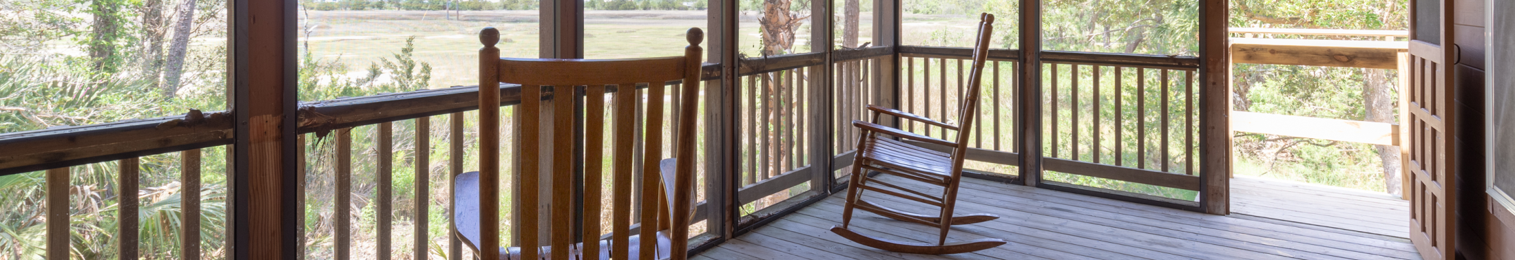 Rocking chairs sit on the screened in porch of the Cottages at James Island County Park