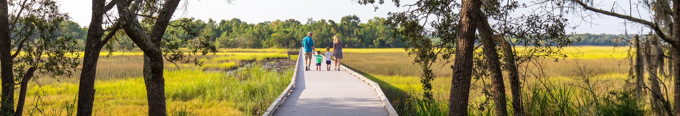 Family of four walks along the boardwalk at Stono River County Park