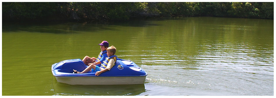 Children enjoying a paddle boat at Camp Rise Above