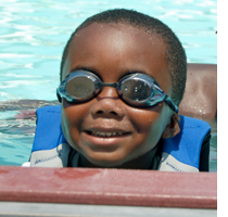Young boy in swim goggles smiling at camera
