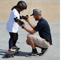Young girl on a skateboard being taught to skate by a SK8 Charleston staff member