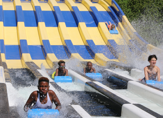 Teenagers sliding down Riptide Run at Whirlin' Waters Adventure Waterpark