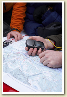 Image of two people with a global positioning system looking over a map