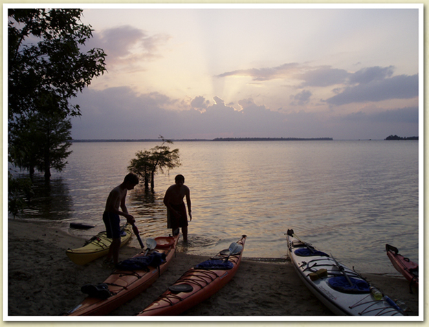 Image of kids on a sandy beach with kayaks at sunset