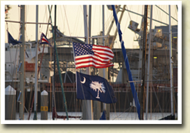 Image of a US flag and a SC state flag flying on the mast of a sailboat