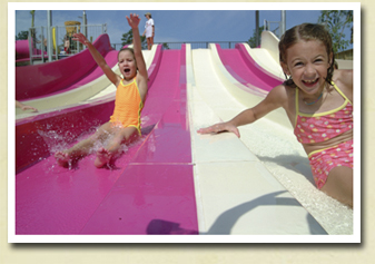 Image of two young girls sliding down a water slide at Whirlin' Waters Adventure Waterpark