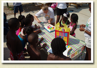 Image of young children gathered around a picnic table with presents and a birthday cake during a birthday party at Whirlin' Waters Adventure Waterpark
